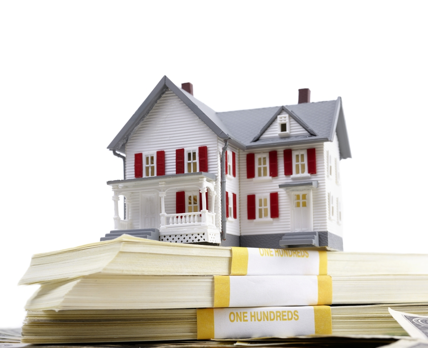 A miniature house over a stack of cash