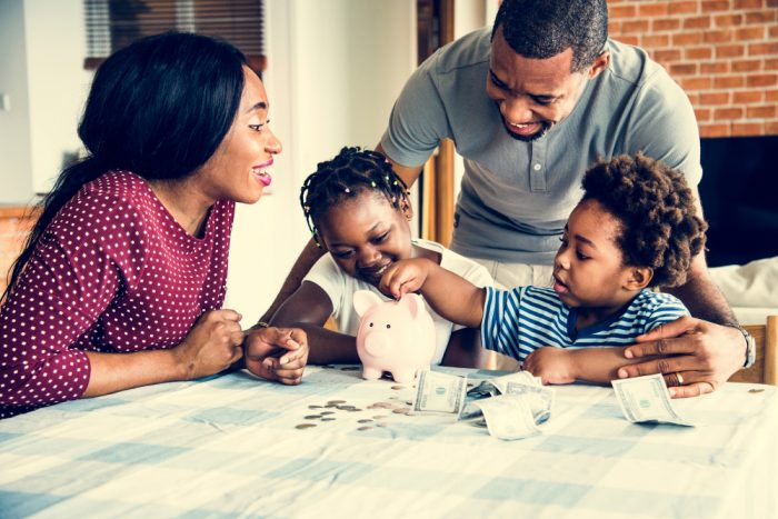 Family of four gather around a piggy bank